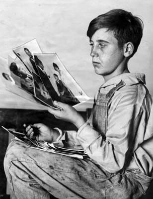 He is shown looking over photos of missing boys. He claimed Walter Collins was a victim and picked his photo out of 30 but could not identify a boy found and returned as Walter Collins.